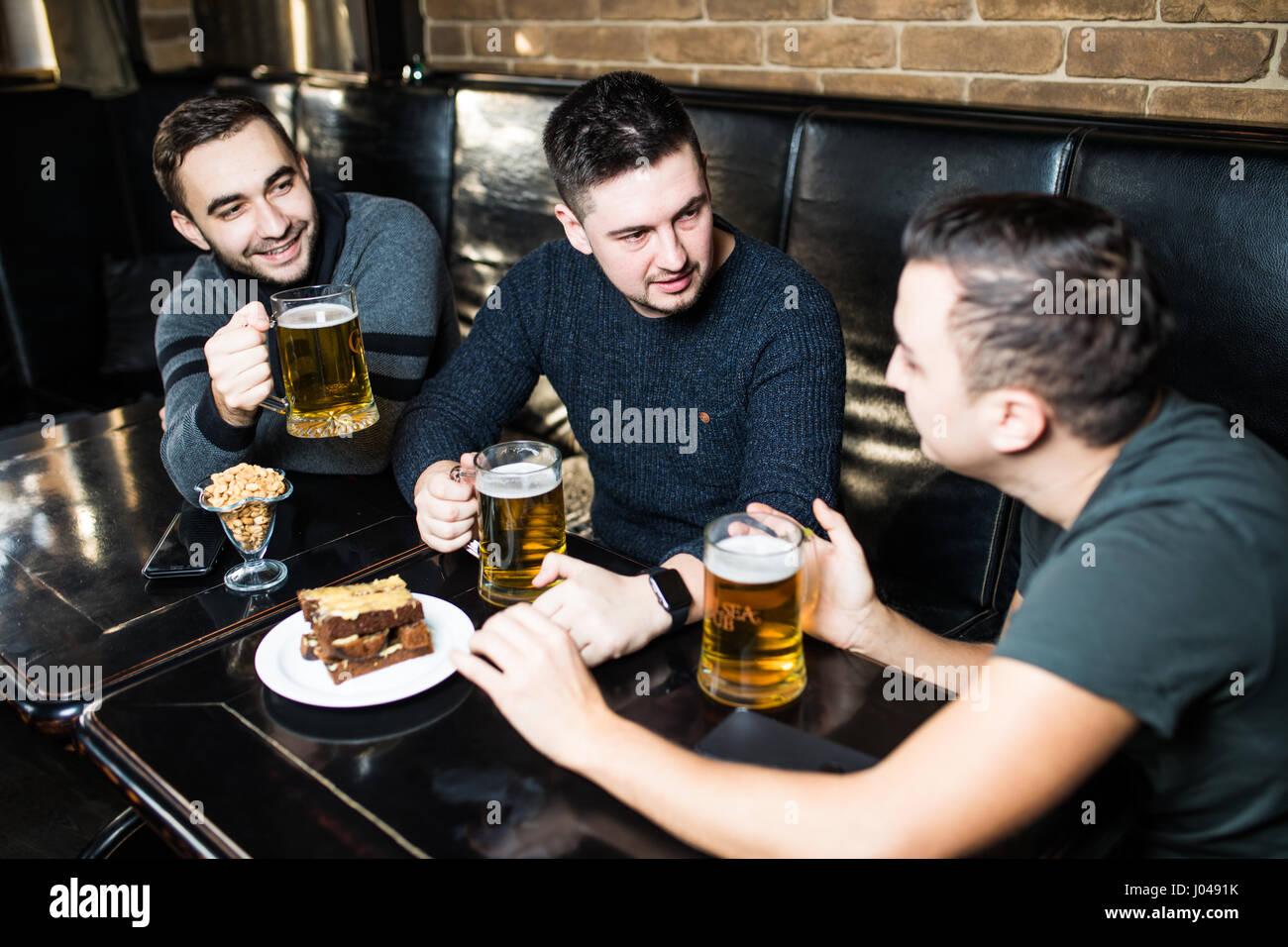 Felice di tre giovani uomini in abbigliamento casual a parlare e a bere birra seduti nel bar insieme Immagini Stock