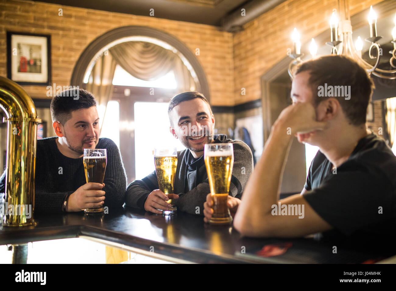 Allegro vecchi amici divertendosi e bere birra presso il bar contatore nel pub. Immagini Stock
