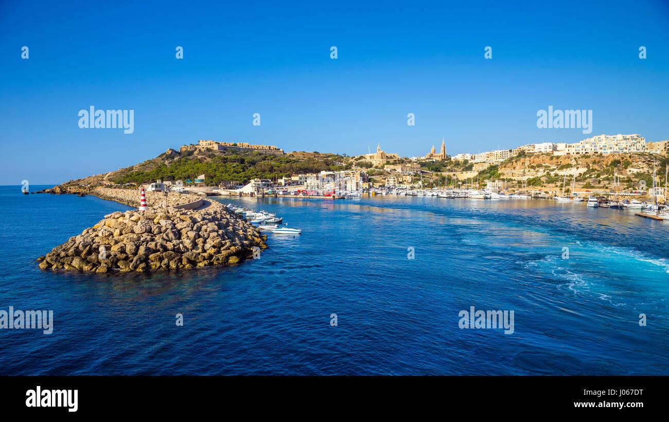 A Gozo, Malta - antico porto di Mgarr con faro sull isola di Gozo su un luminoso giorno di estate con il mare blu Foto Stock