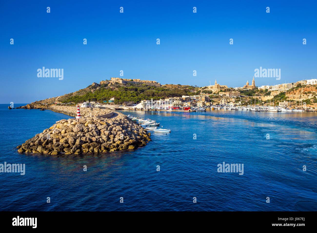 A Gozo, Malta - antico porto di Mgarr con faro sull isola di Gozo su un luminoso giorno di estate con il mare blu Immagini Stock