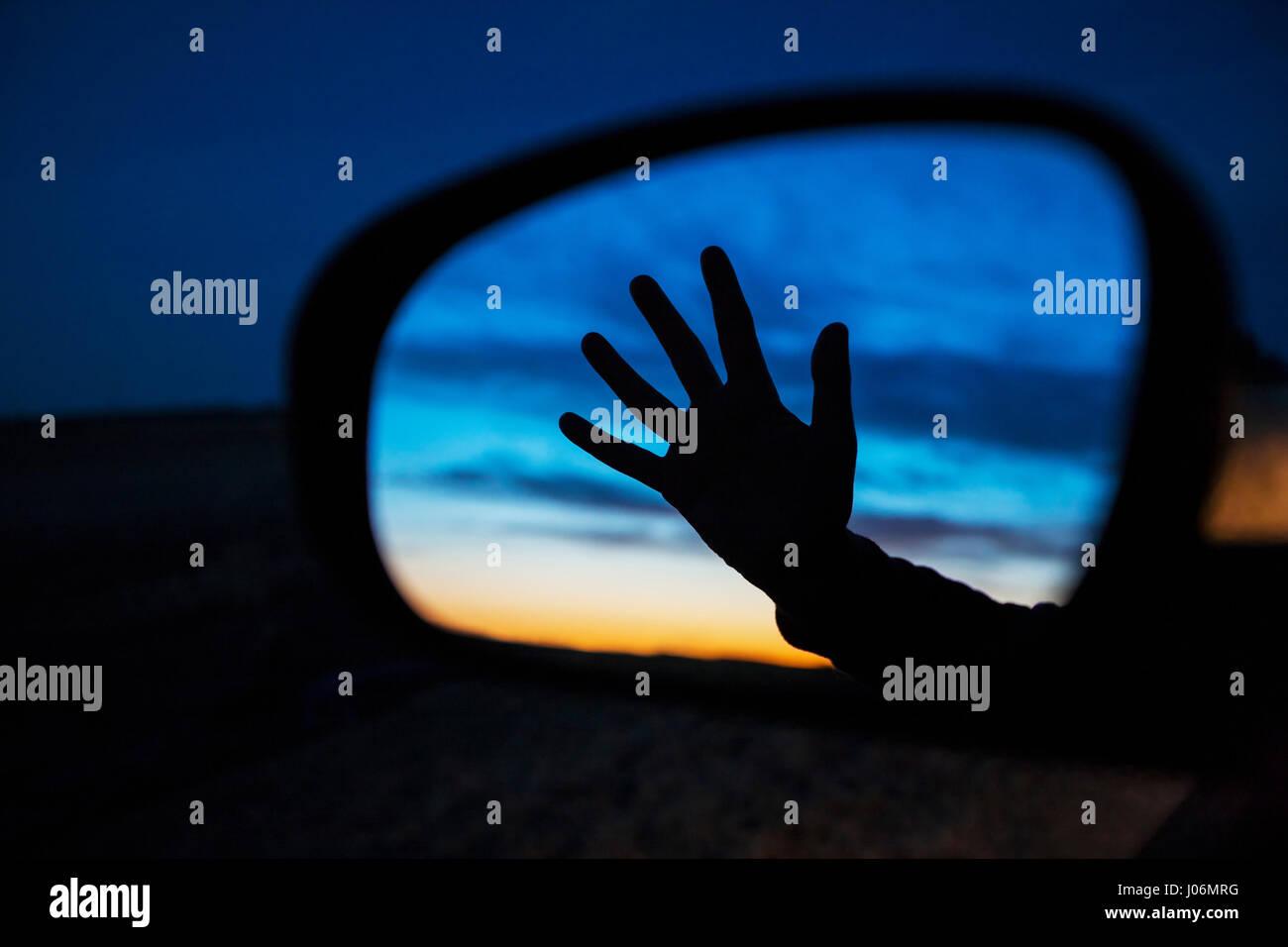 Silhouette a mano nel lato specchio auto di notte Immagini Stock