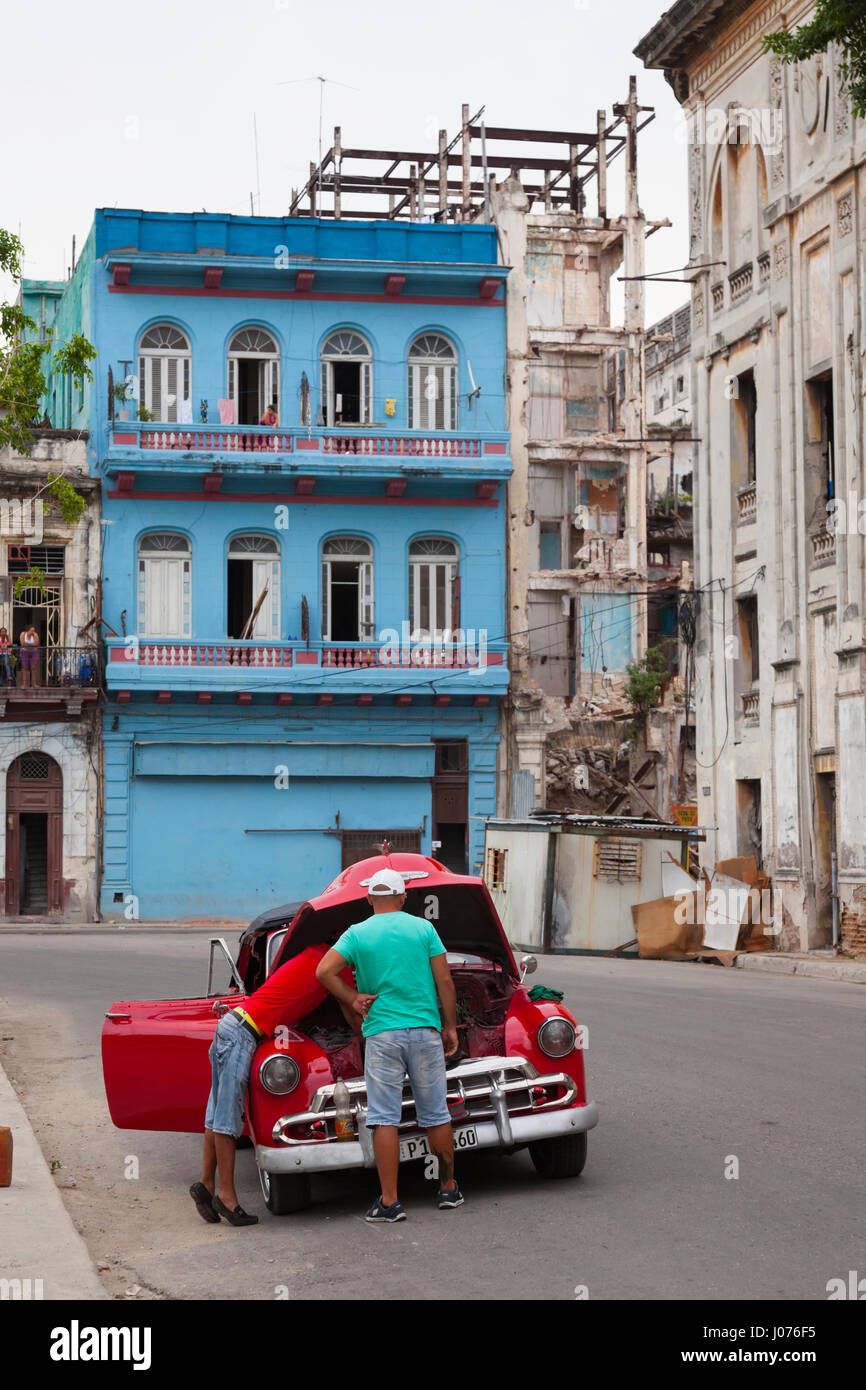 Due uomini cubani che fissa la loro auto in mezzo alla strada nella Vecchia Havana, Cuba. Immagini Stock