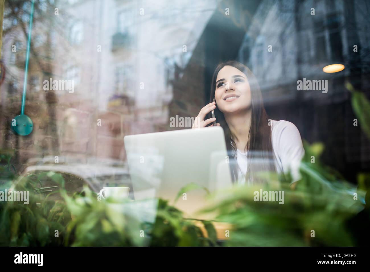 Giovane donna parla al telefono in coffee shop Immagini Stock