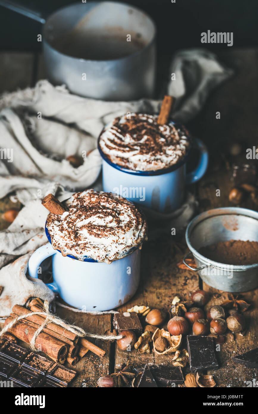 Cioccolata calda con panna montata, bastoncini di cannella e i dadi Immagini Stock