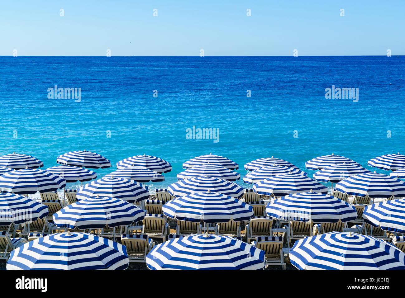 Blu e bianca spiaggia ombrelloni, Nizza, Alpes Maritimes, Cote d'Azur, Provenza, Francia, Mediterranea Immagini Stock