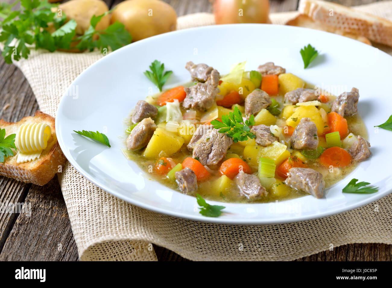 In casa e la lenta cottura stufato irlandese con carne di agnello e patate e altri ortaggi o legumi Immagini Stock