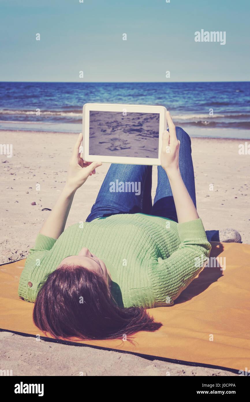 Giovane donna utilizza computer tavoletta su una spiaggia, schermata vuota per copiare lo spazio, retro vintage Immagini Stock