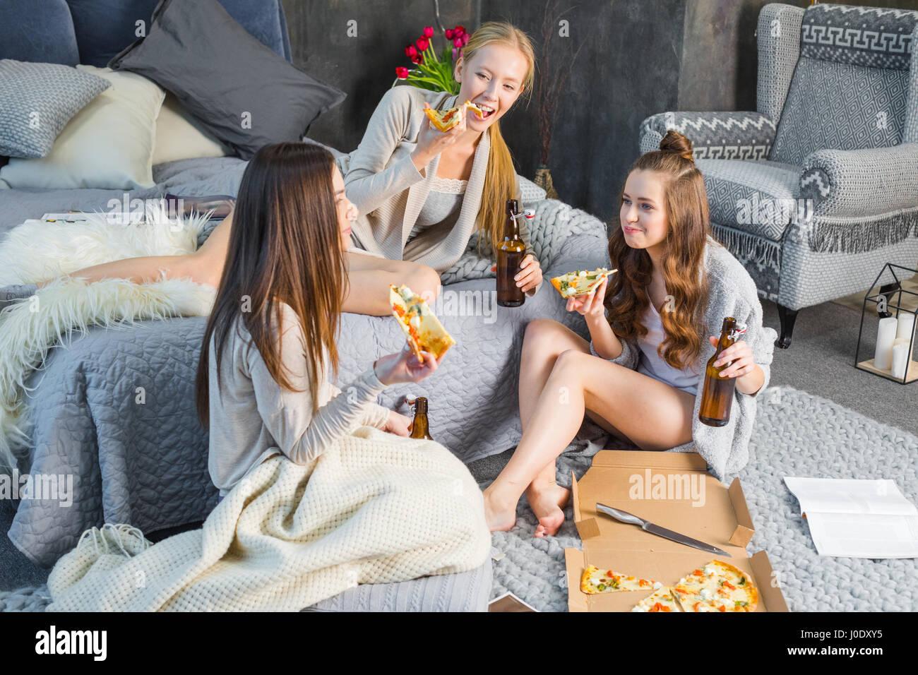 Tre giovani sorridente amiche di mangiare pizza e bere birra in