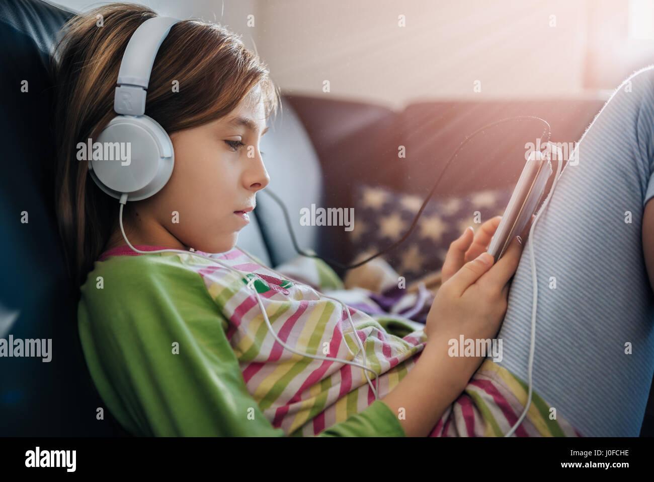 Ragazza seduta sul divano nero utilizzando tablet e ascolto di musica Immagini Stock