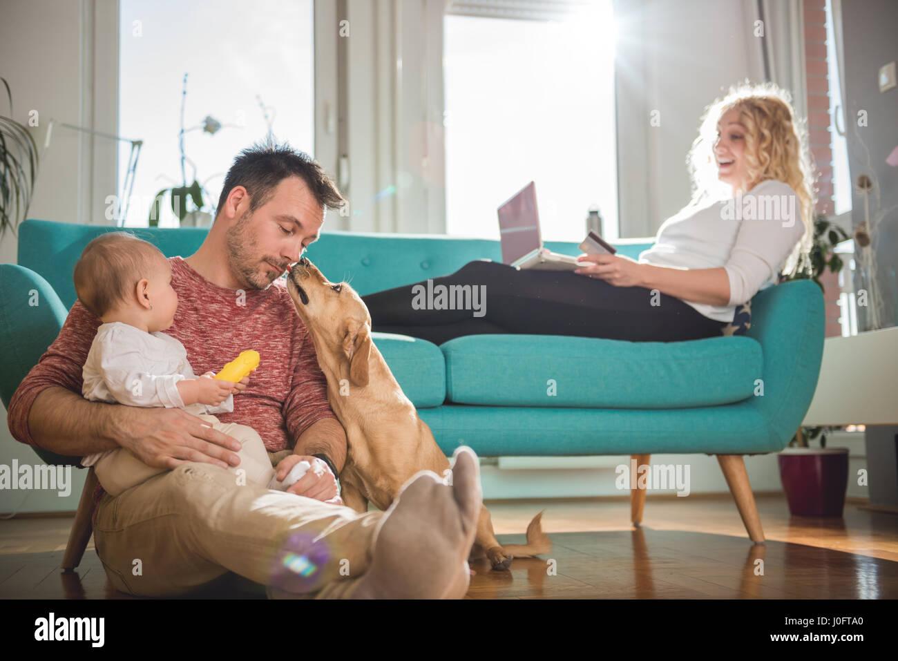 Padre seduto sul pavimento e con il bambino tra le braccia a giocare con il cane mentre la moglie seduta sul divano Immagini Stock