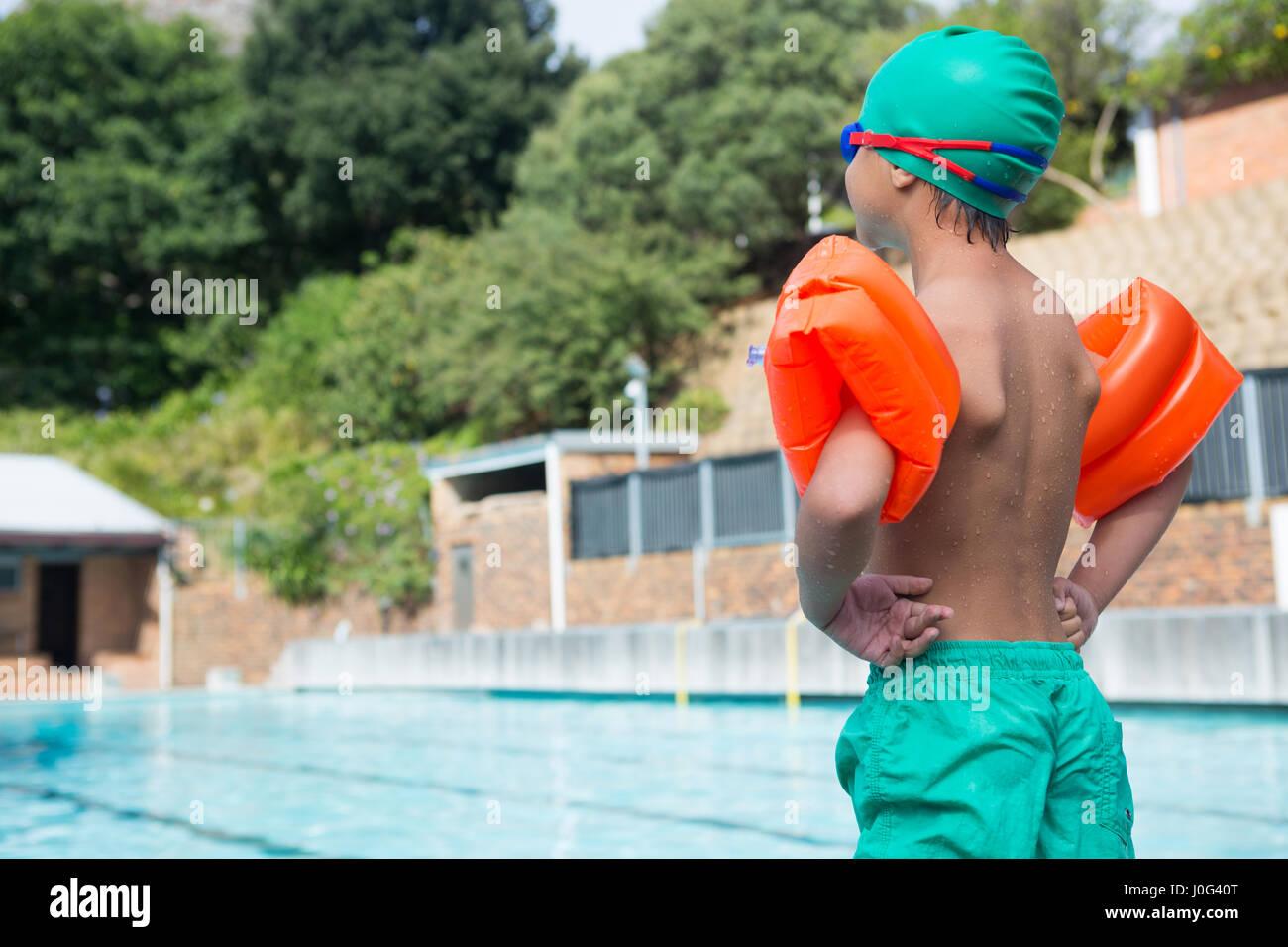 Vista posteriore del ragazzo che indossa fascia braccio in piedi sul bordo della piscina Foto Stock