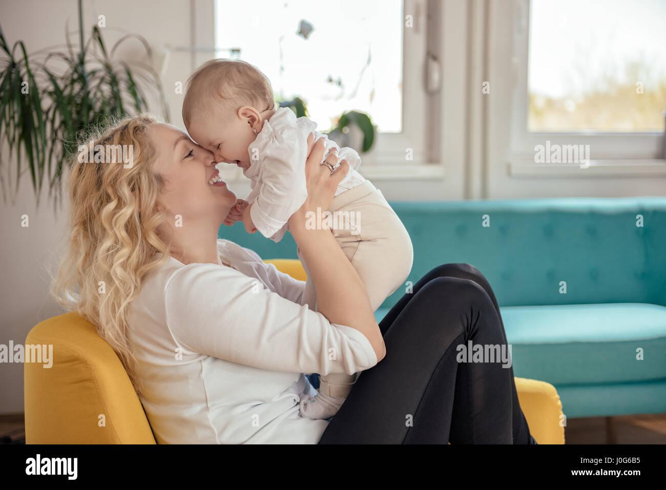 La madre e il suo bambino testa a testa seduto in poltrona di colore giallo Immagini Stock