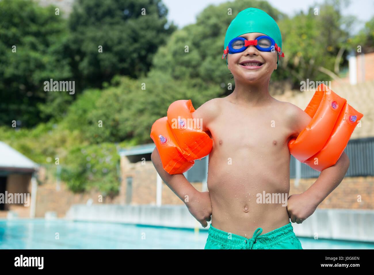 Ritratto di ragazzo indossa fascia braccio in piedi sul bordo della piscina Foto Stock