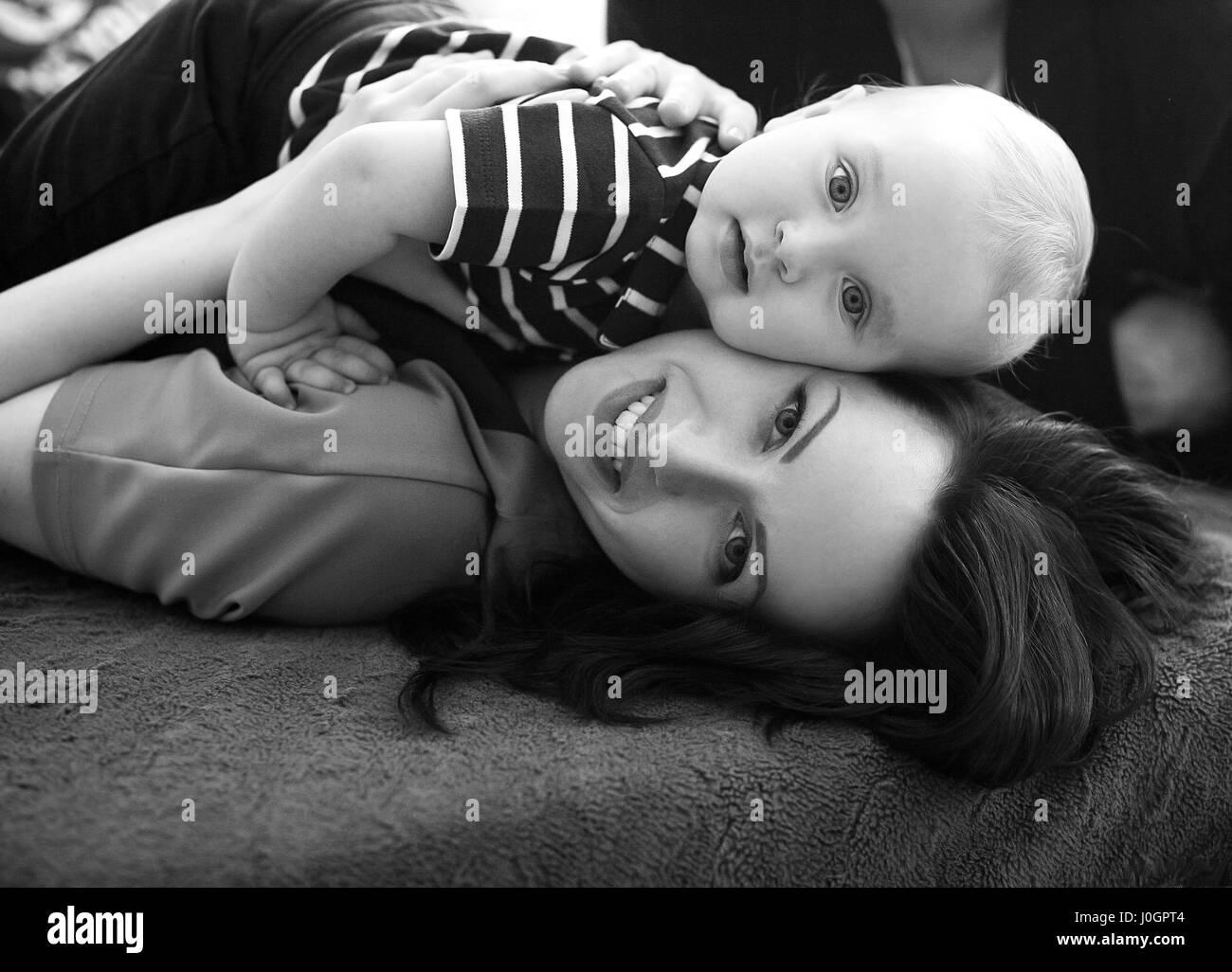 Giovane madre giace sul letto con il suo bambino e abbracci di lui ...