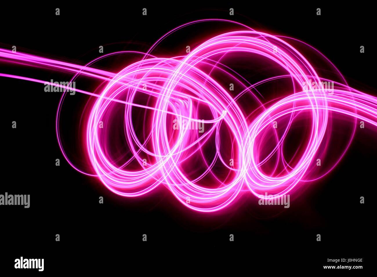 Luce rosa fotografia pittura - Lunga esposizione foto di rosa vibranti anse e volute su sfondo nero. Abstract pattern Foto Stock