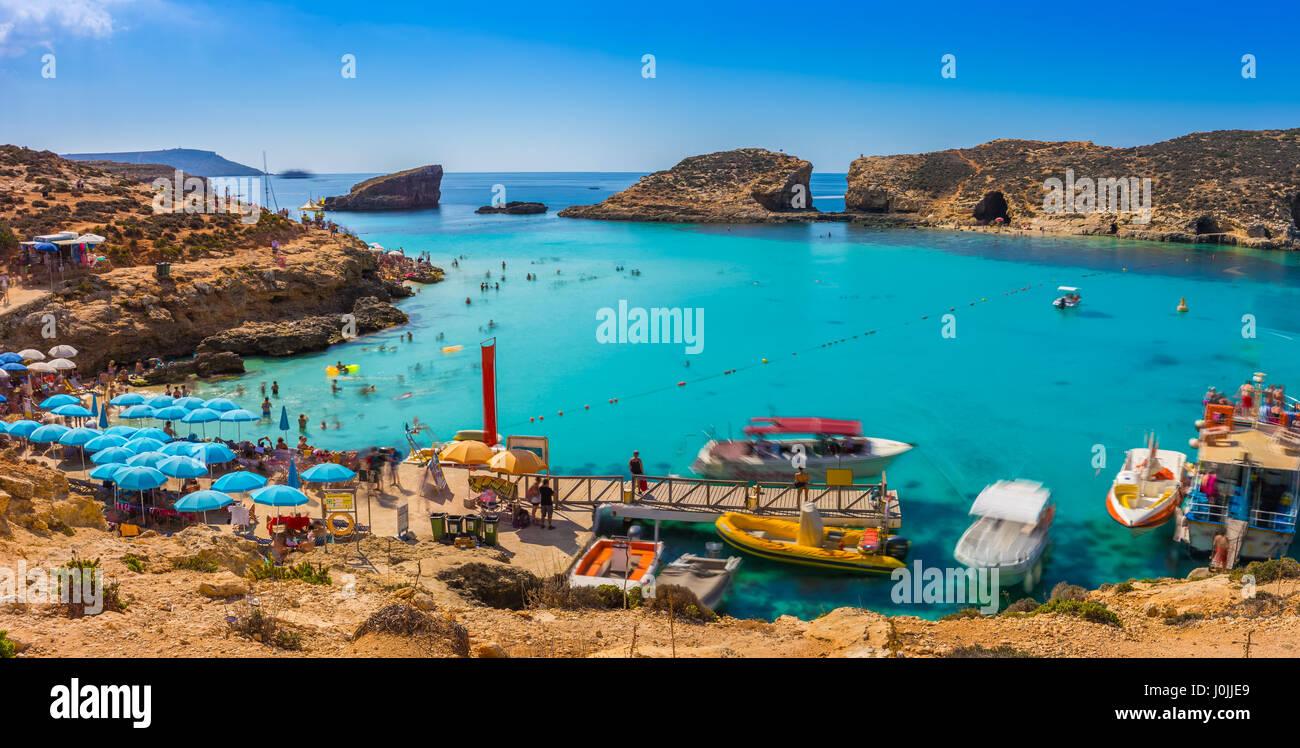 A Comino e Malta - i turisti affollano alla Laguna Blu per godersi le limpide acque turchesi su una soleggiata giornata Immagini Stock