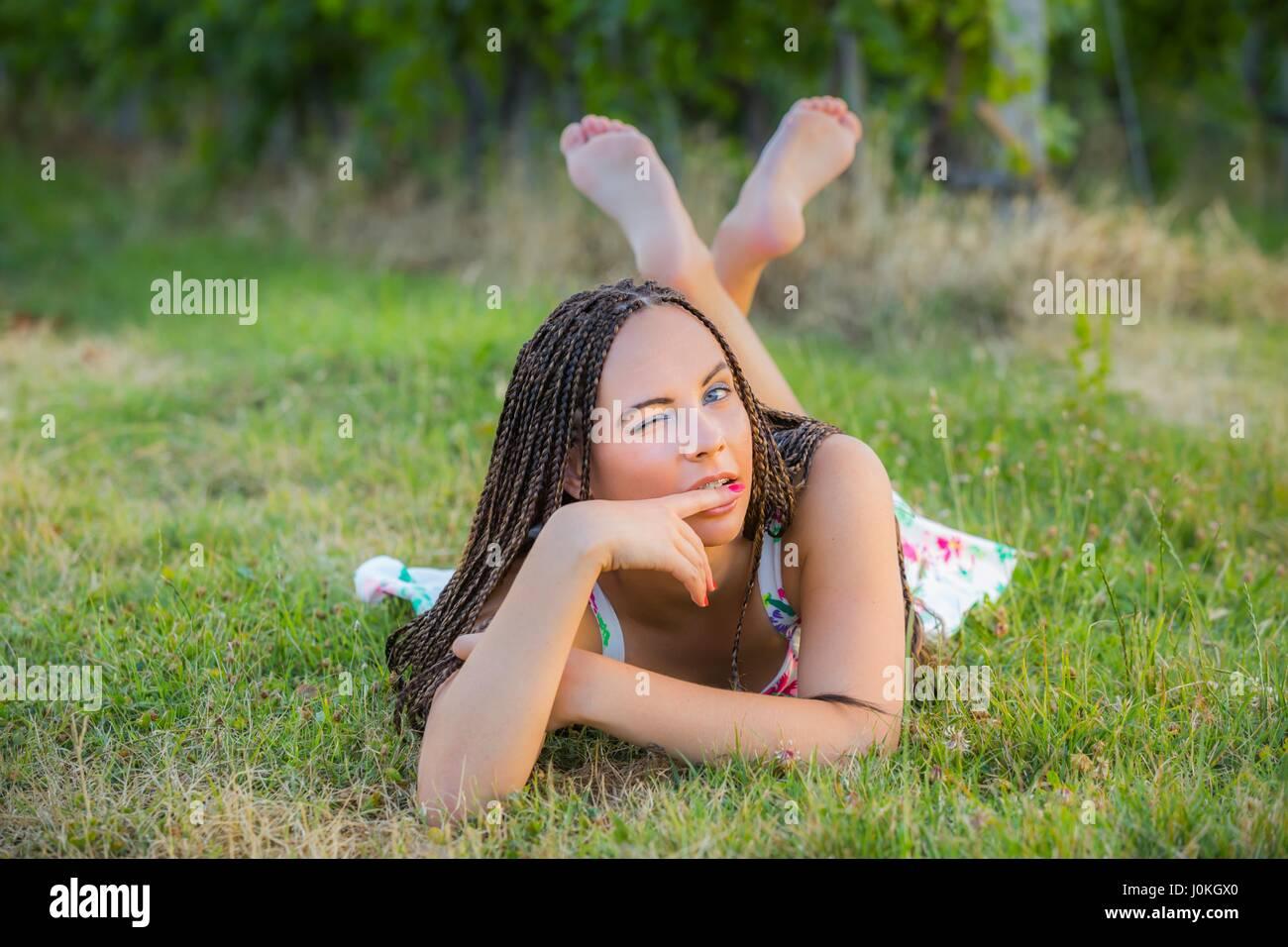 Paese Teen-ragazza distesa sulla pancia di erba winking un occhio guardando gli occhi della telecamera a contatto di lunghezza completa scalza cross zampe gambe incrociate naturelover Foto Stock