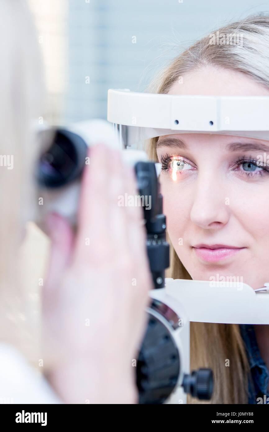 Paziente di sesso femminile avente occhio in esame all'ottico optometrista del negozio, close-up. Foto Stock