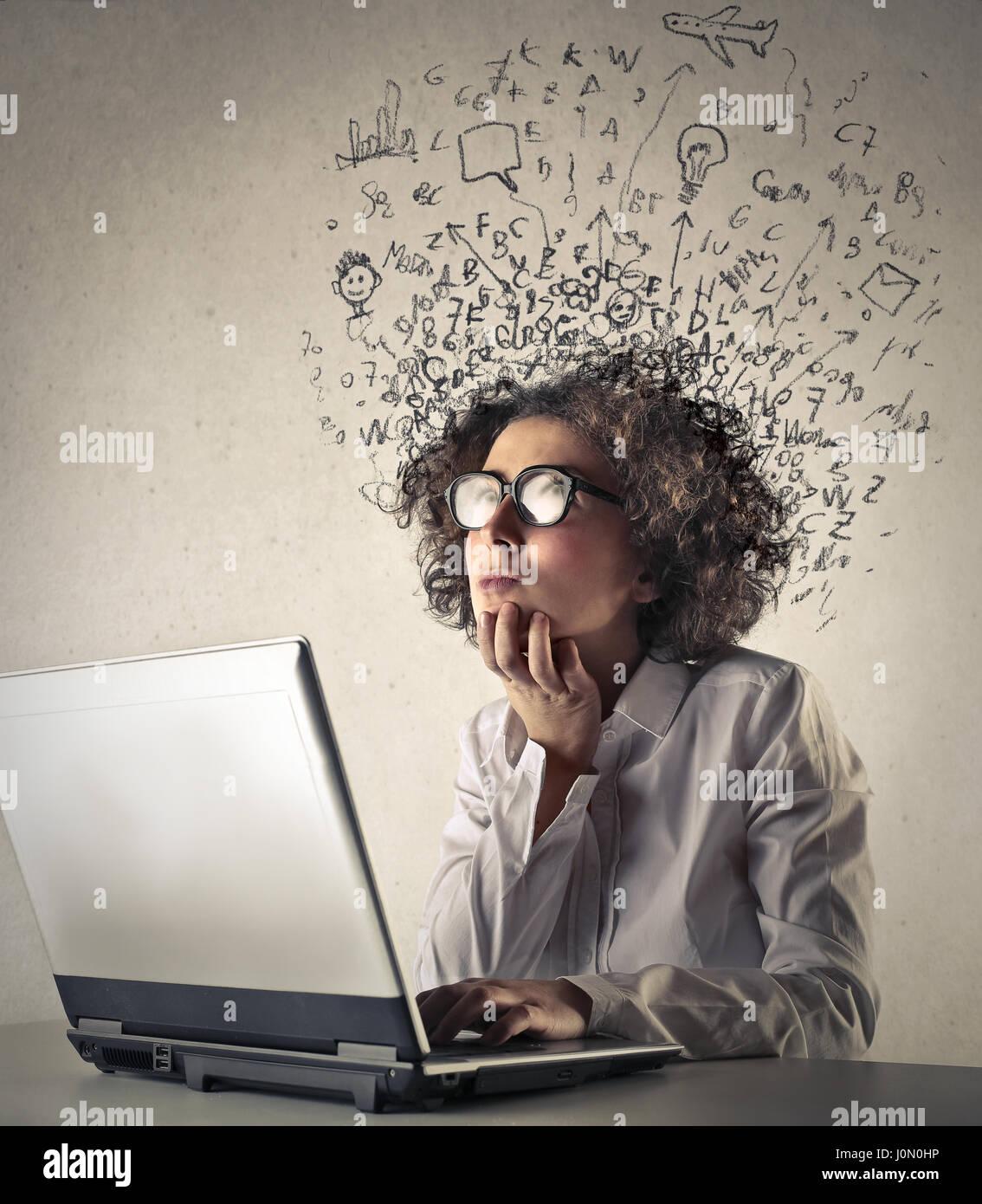 Donna pensando nella parte anteriore del computer portatile Immagini Stock