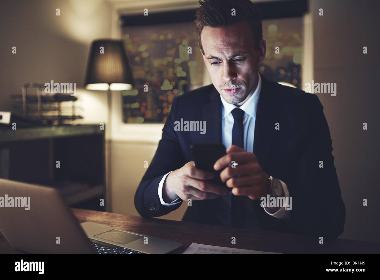 La persona intelligente con il suo smartphone al lavoro di notte. Immagini Stock