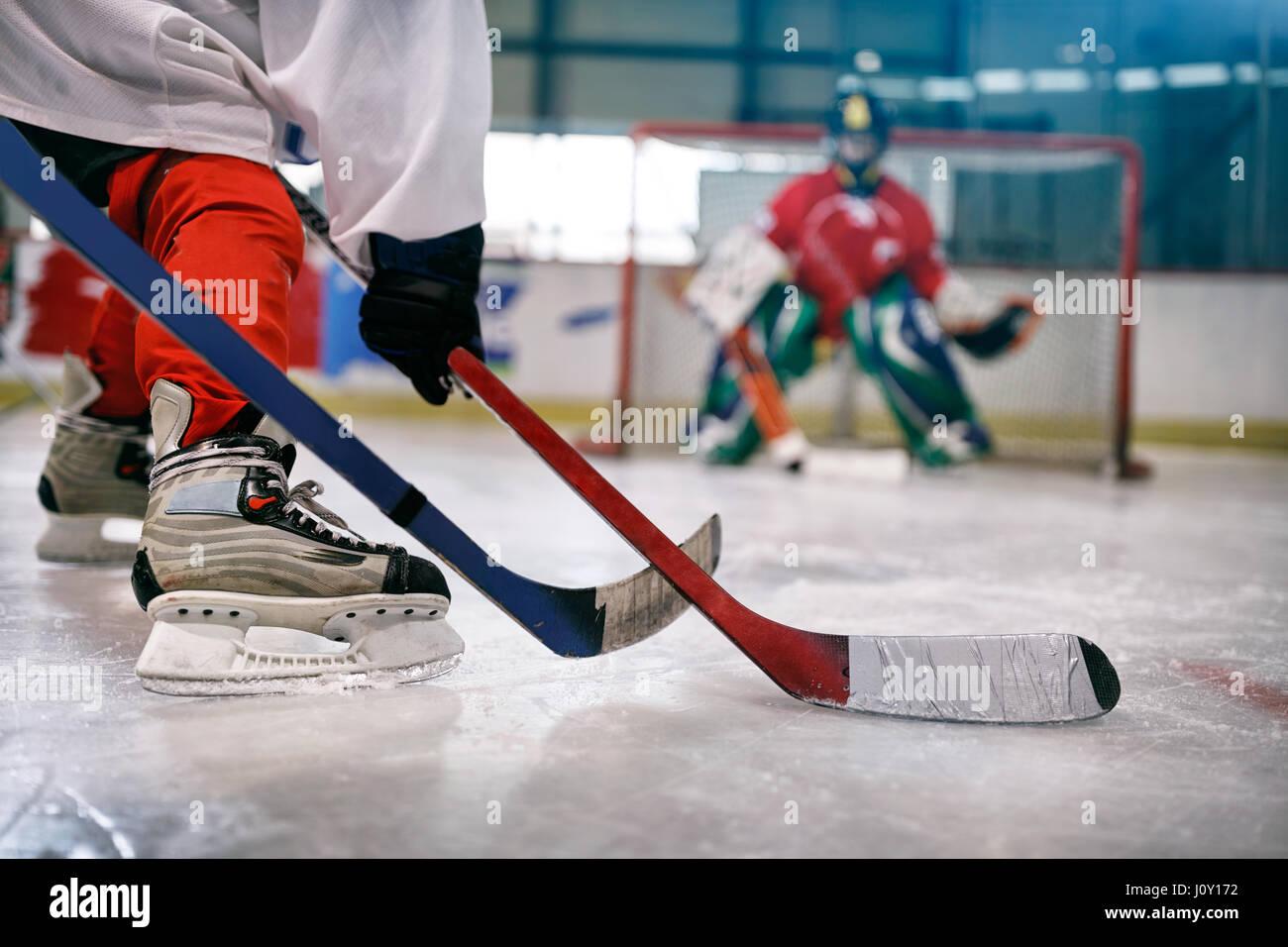 Hockey su ghiaccio giocatore in azione calci con bastone sul traguardo Immagini Stock