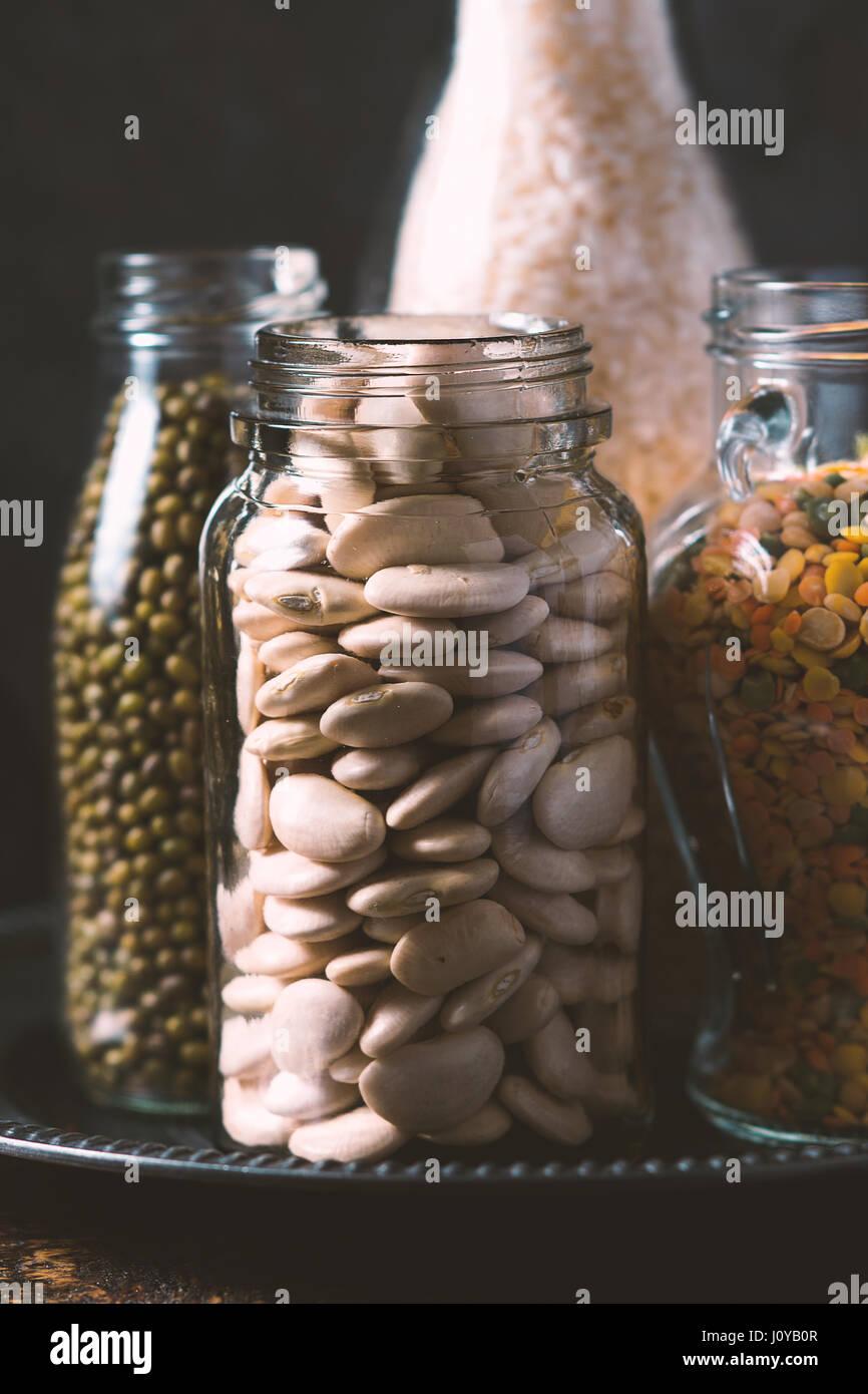 Riso e lenticchie, fagioli bianchi in bottiglie vista laterale verticale Immagini Stock