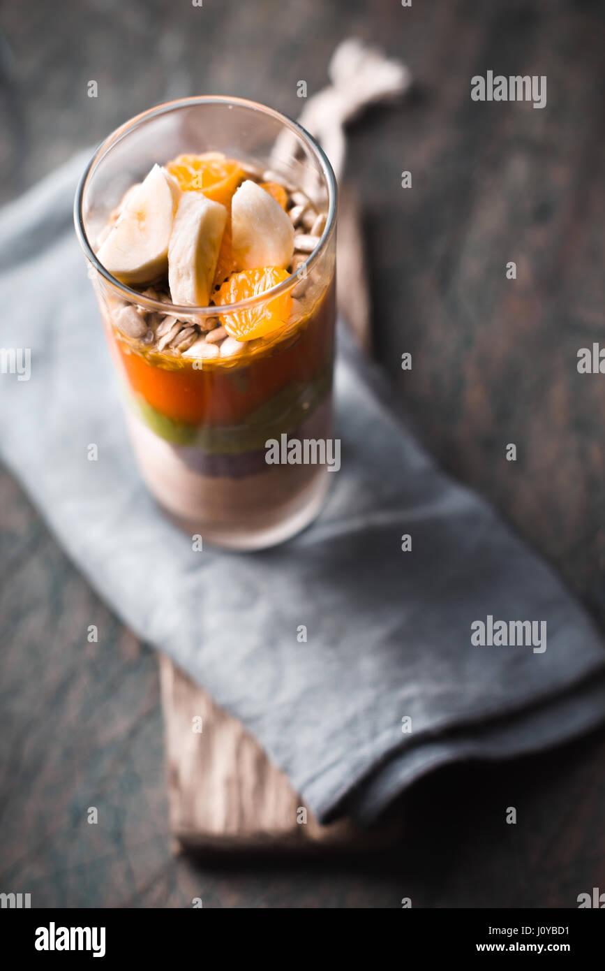 Frutta e yogurt dessert sullo sfondo sfocato verticale Immagini Stock