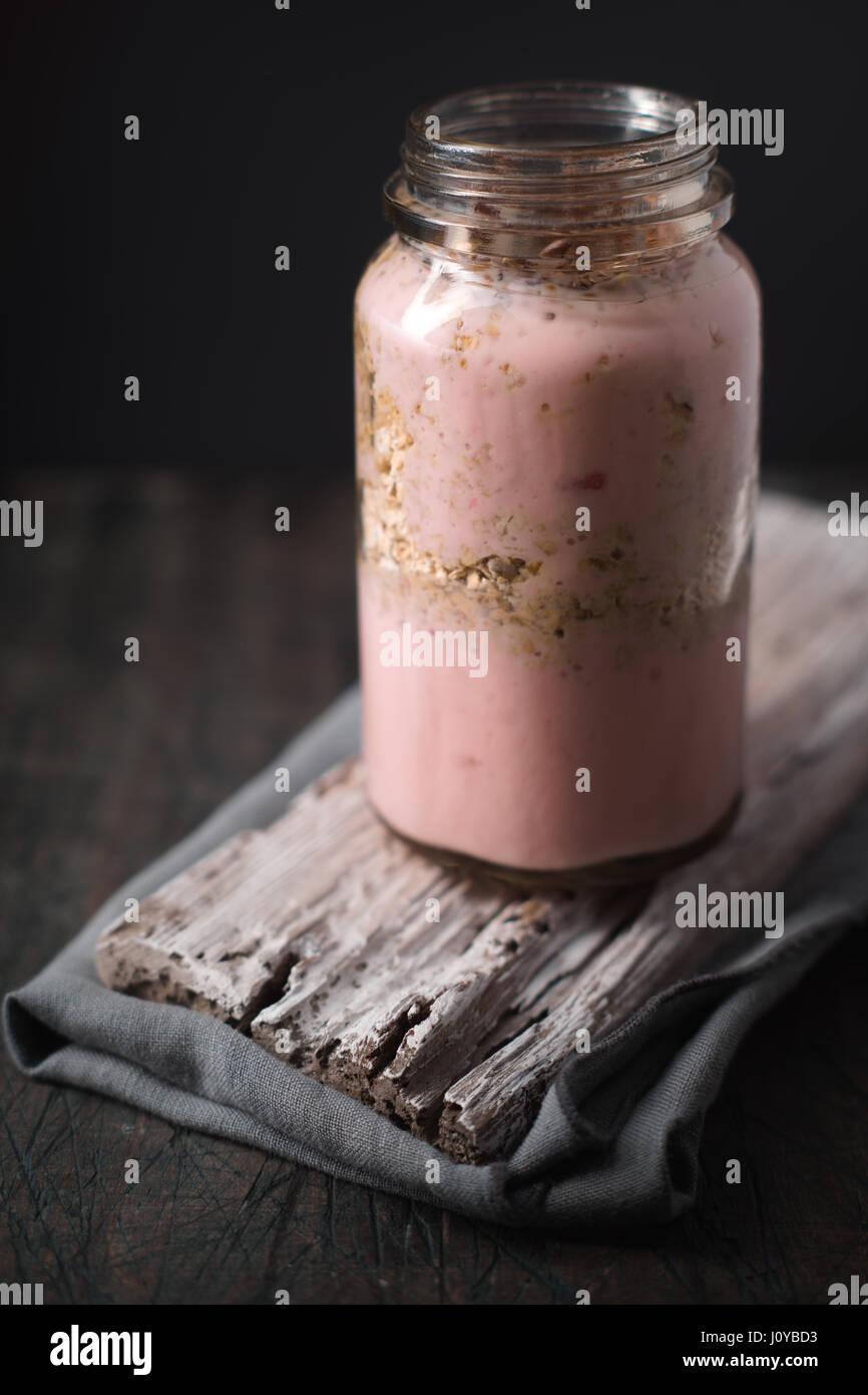 Yogurt sano sul tavolo di legno in verticale Immagini Stock