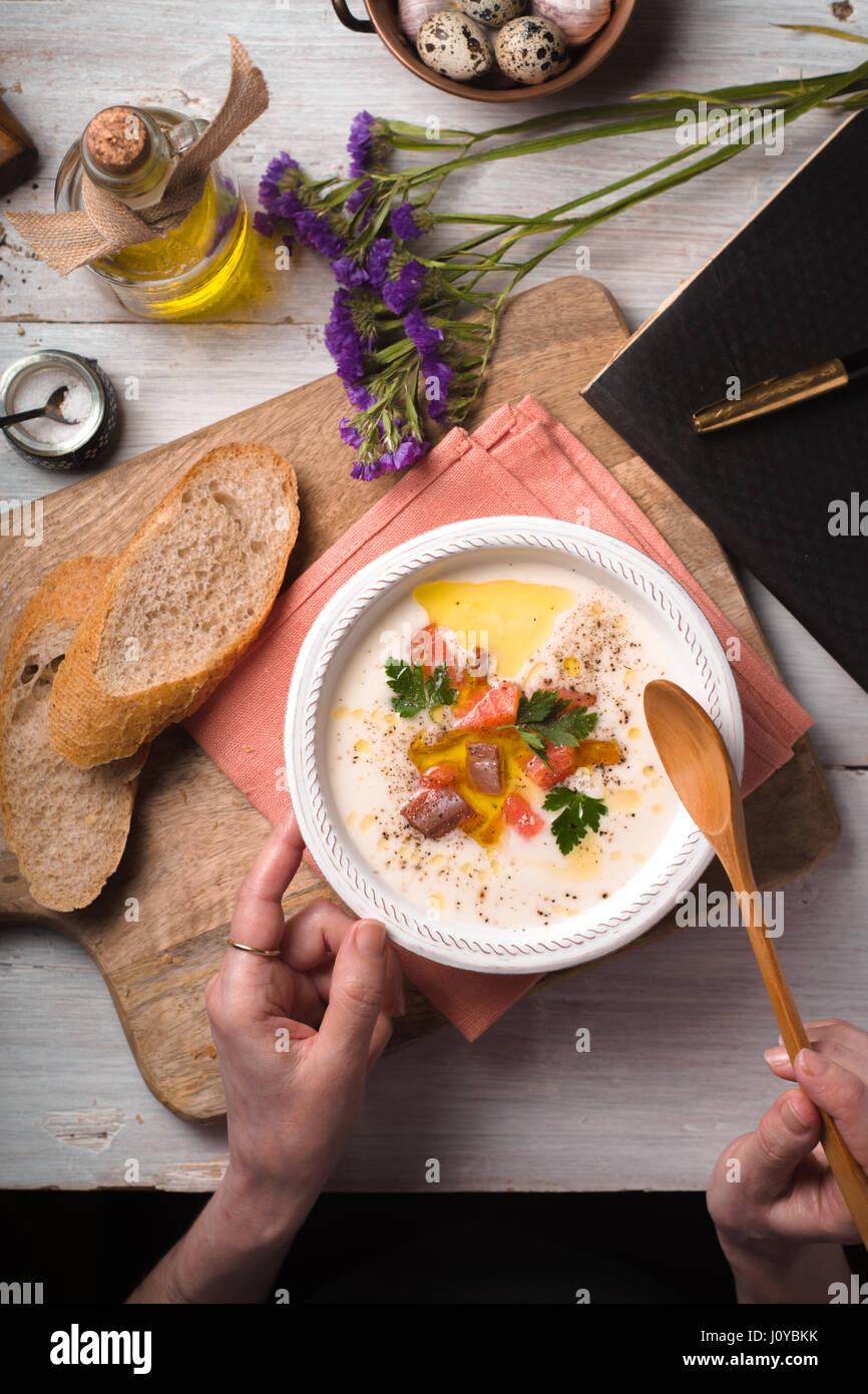 Donna di mangiare la minestra con purea di salmone da un vaso di ceramica Immagini Stock