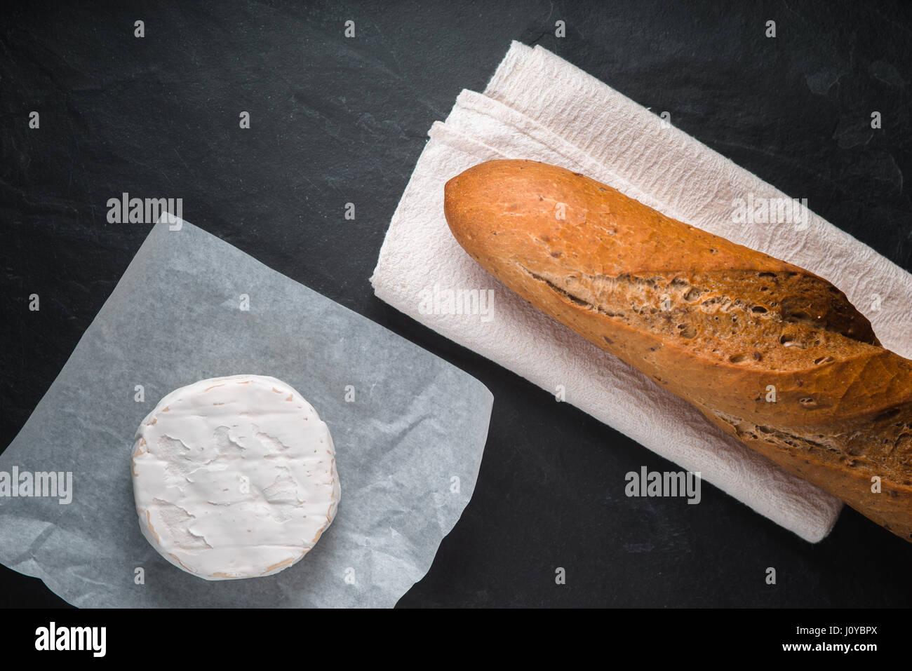 Formaggio Brie e baguette al buio su un tavolo Immagini Stock