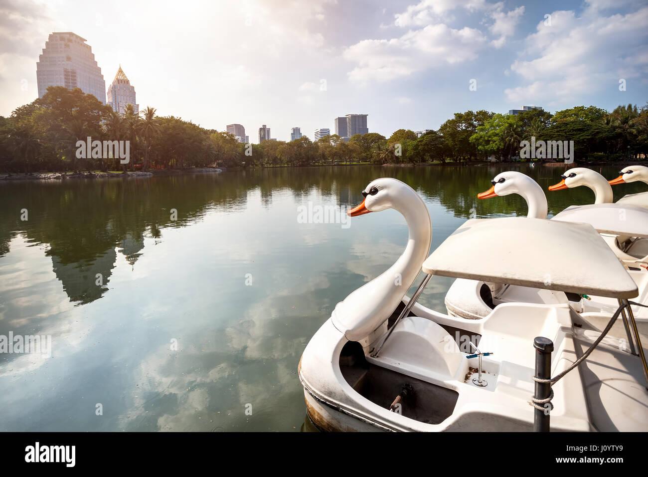 Il lago e la barca a forma di cigno bianco nel Centro Parco Lumpini di Bangkok, Thailandia Immagini Stock