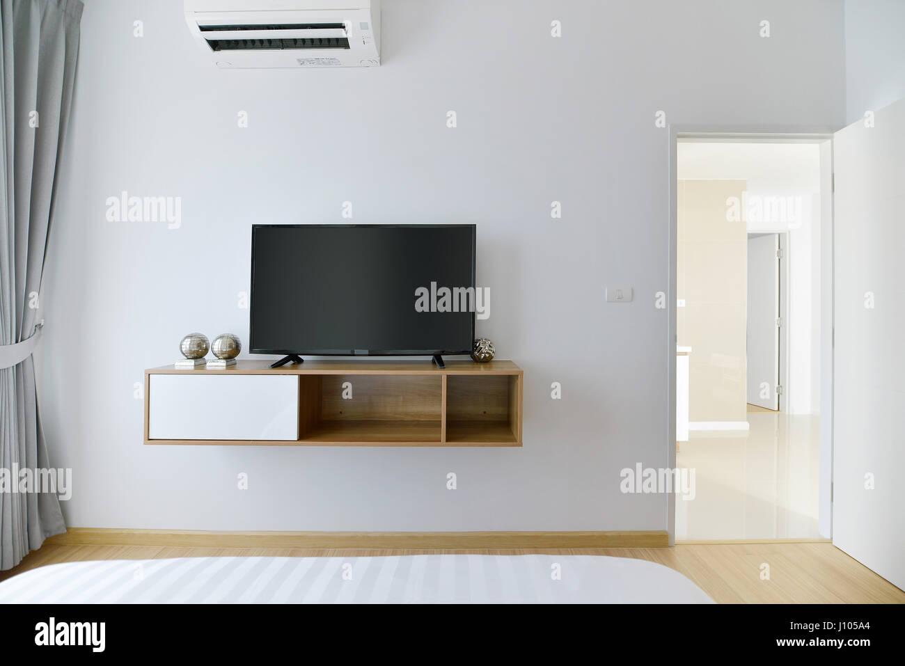 Moderna camera da letto vuoto con led tv sul muro bianco e ripiano ...