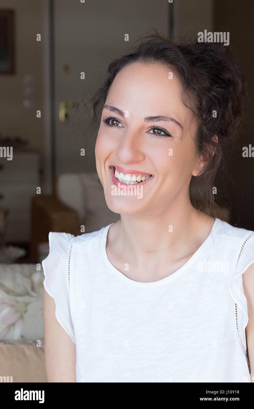 Portra di un greco giovane donna sorridente, felice, guardando lontano, in interni. Immagini Stock