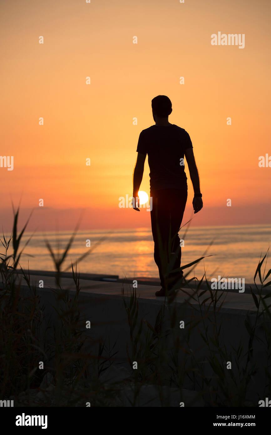 Lunghezza completa silhouette di una figura maschile di camminare sulla spiaggia al tramonto Immagini Stock