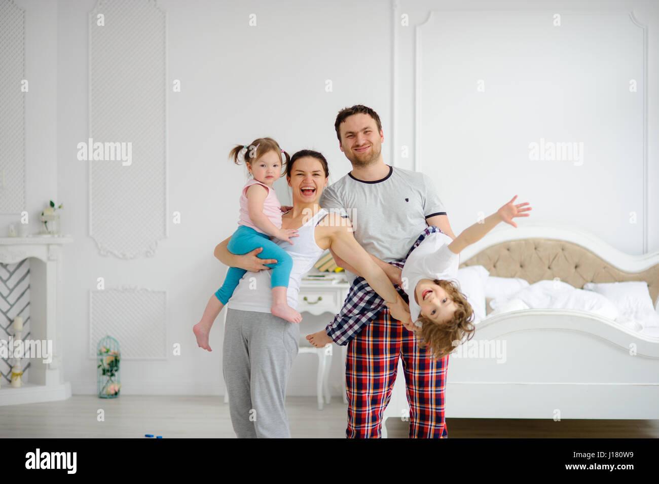 Allegro inizio di giornata in una famiglia felice. Accogliente camera da letto. I giovani genitori tenere sulle Immagini Stock
