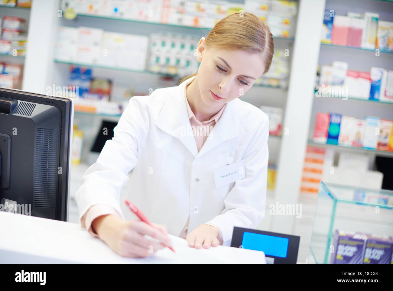 I giovani adulti il farmacista al registratore di cassa scrivania Immagini Stock