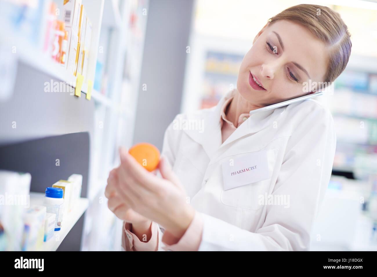 Il farmacista femmina su chiamata telefonica raggiungendo il farmaco Immagini Stock