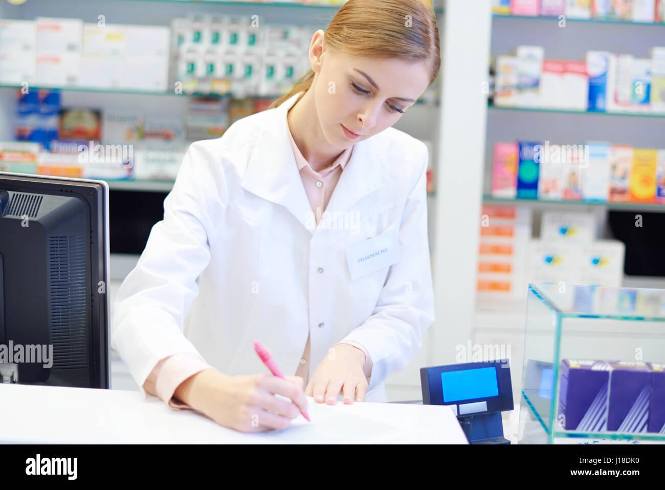 Il farmacista femmina facendo doveri giornalieri Immagini Stock