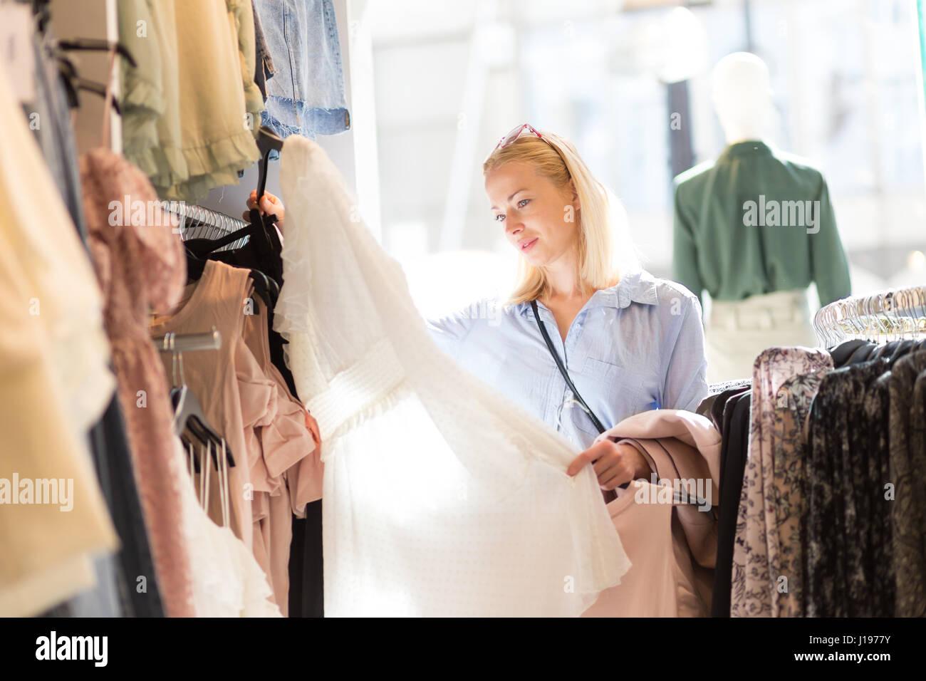 Bella donna shopping abiti alla moda nel negozio di abbigliamento. Immagini Stock