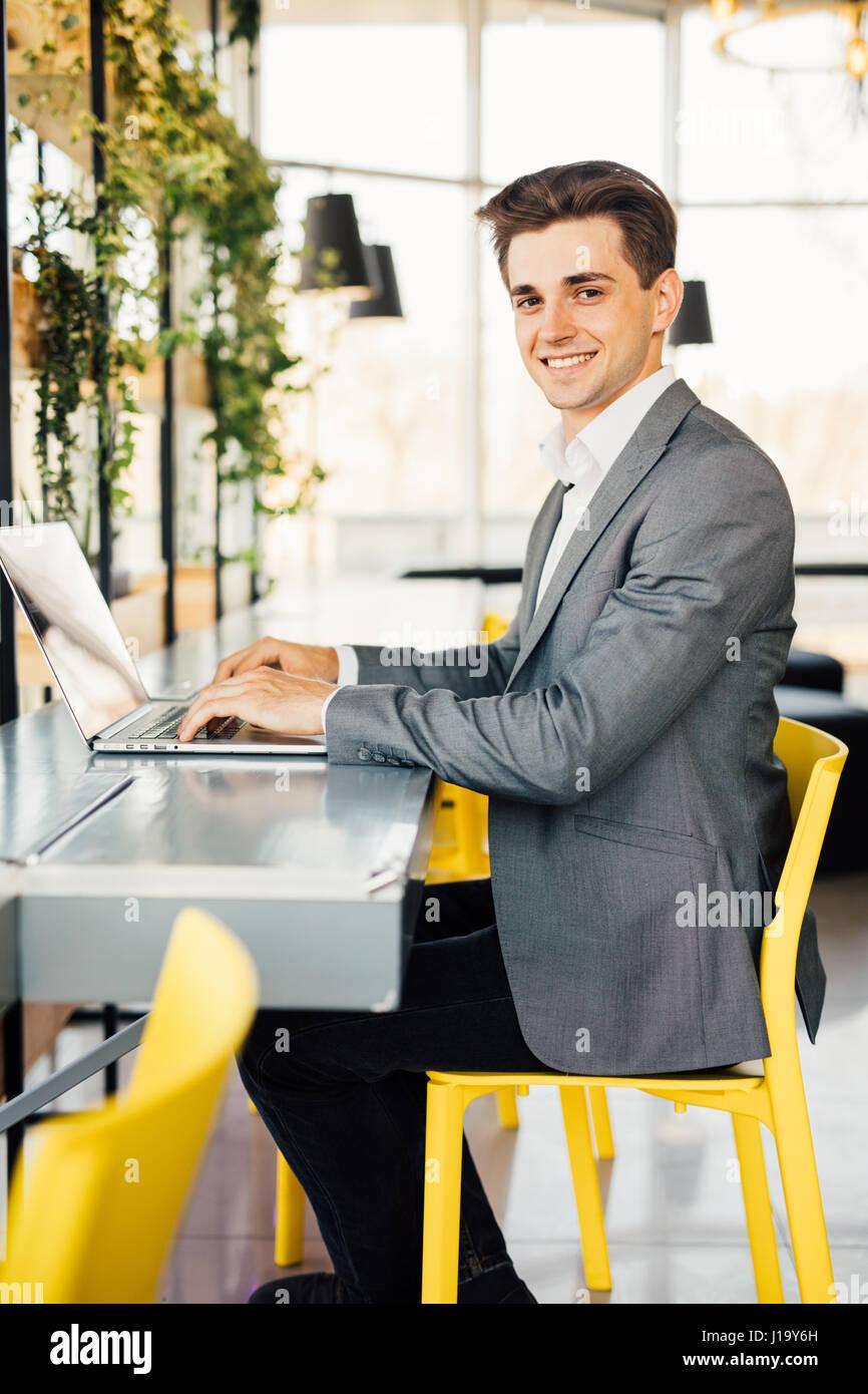 Vista laterale di sorridere uomo d affari seduti a tavola con computer portatile e guardando la fotocamera. Immagini Stock