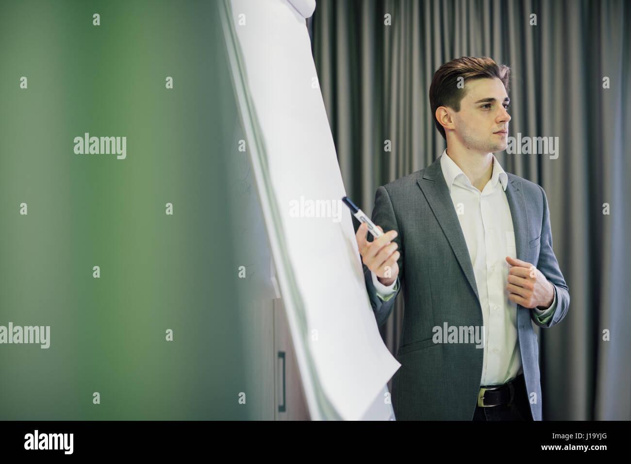 Ritratto di un imprenditore fiducioso rendendo la presentazione sulla lavagna a fogli mobili Immagini Stock