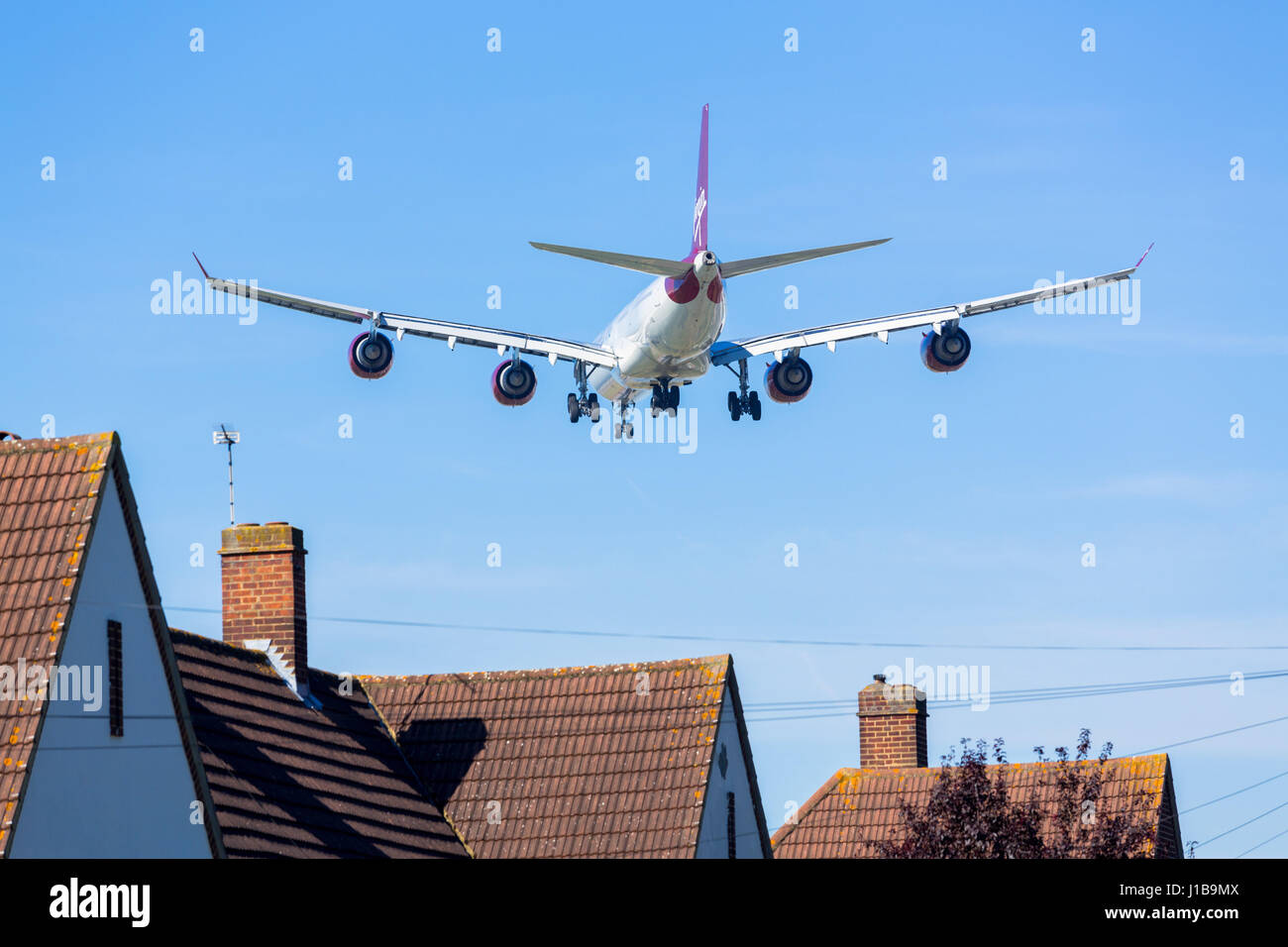 Aerei volando a bassa quota sopra le case causando il rumore inquinamento, l'aeroporto di Heathrow di Londra, Immagini Stock