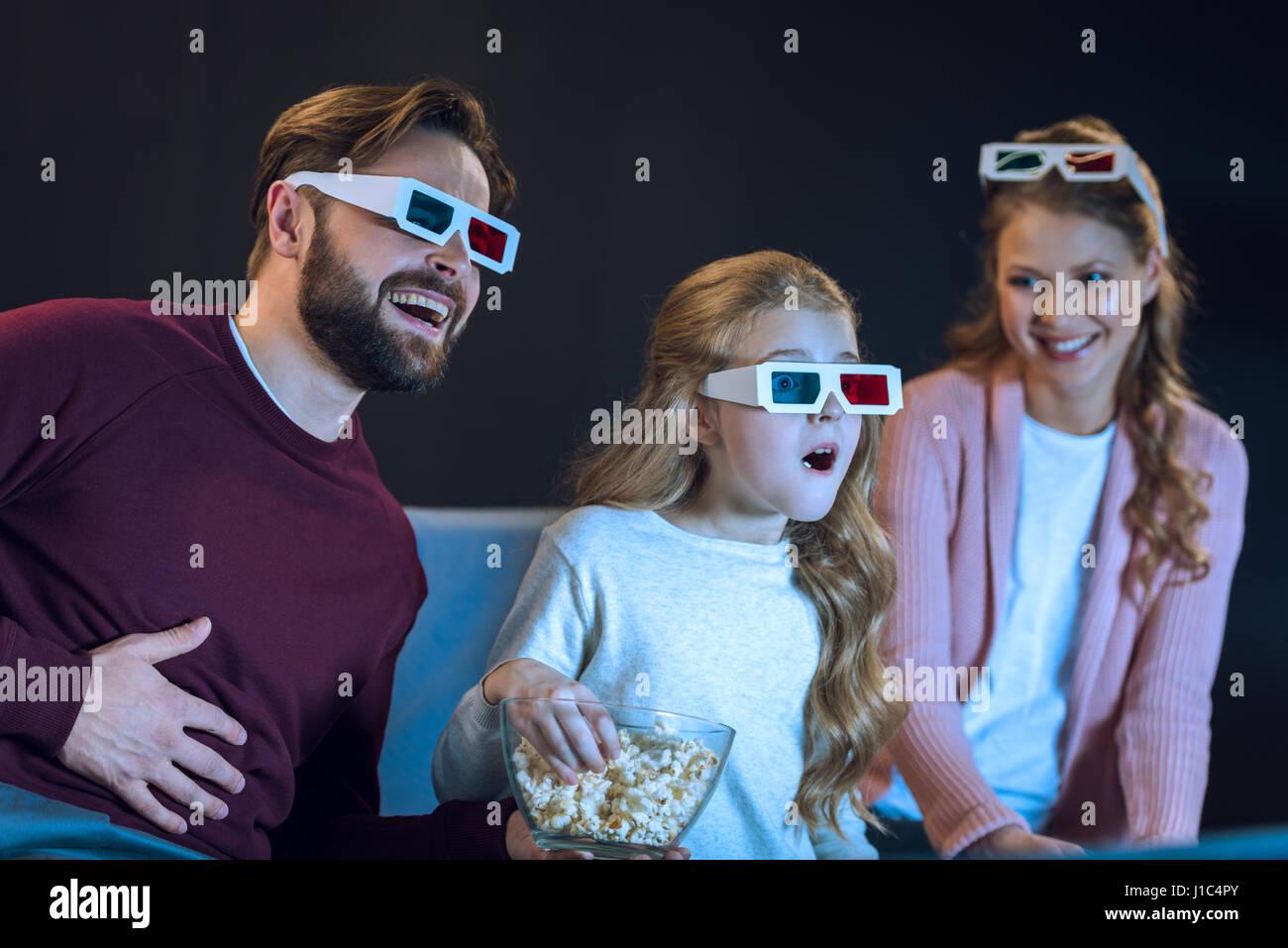 Ridendo famiglia in occhiali 3D per guardare film e mangiare popcorn sul divano Foto Stock