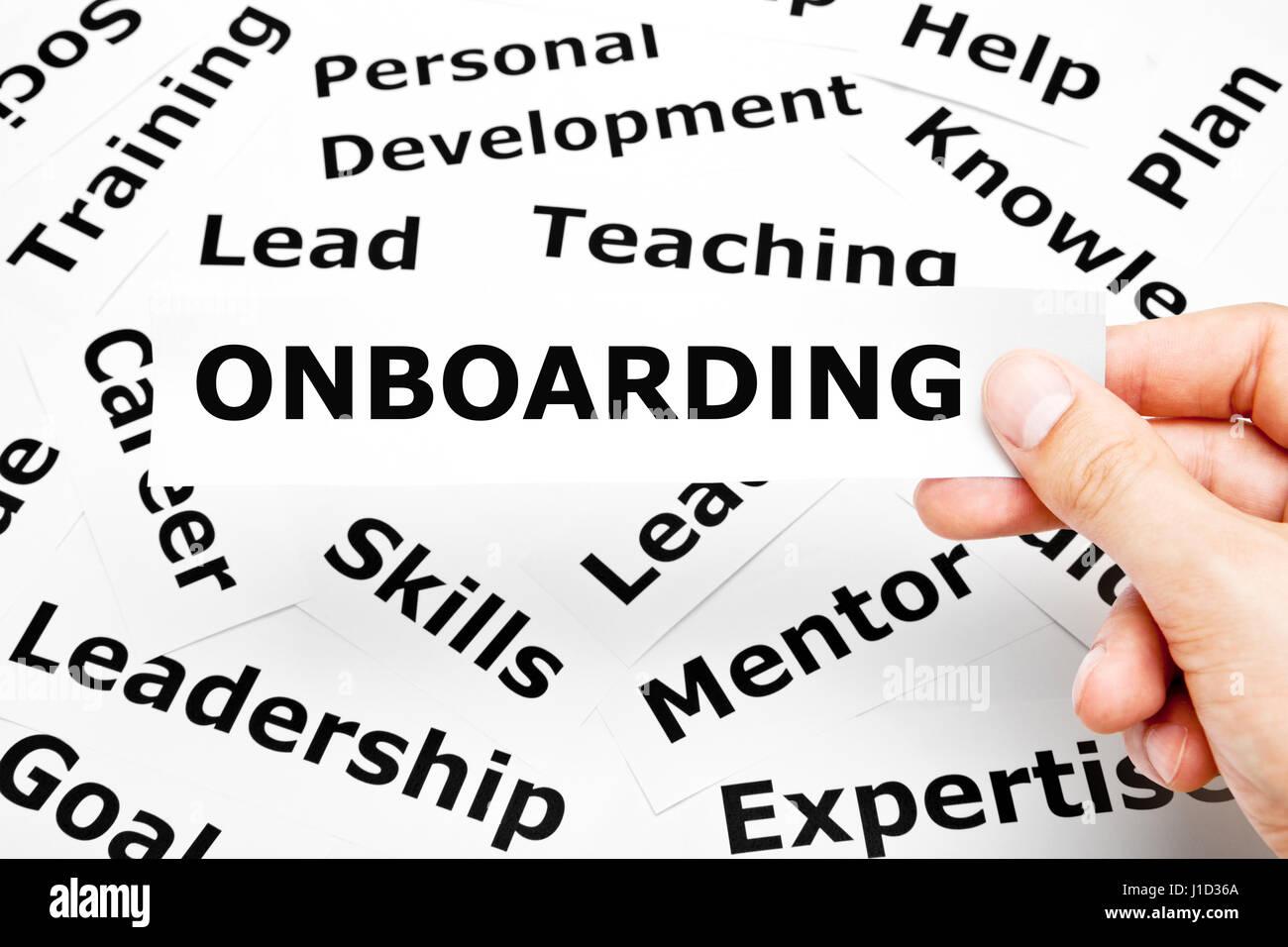 Mano che tiene un pezzo di carta con la parola Onboarding su di essa al di sopra di altre parole correlate sullo Immagini Stock