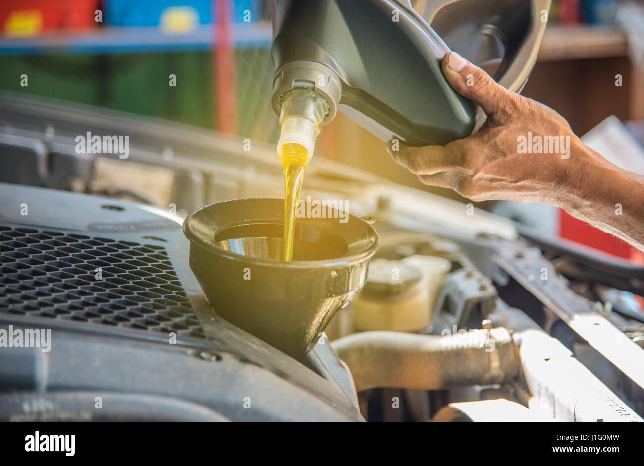 Auto manutenzione manutenzione meccanico versando olio nuovo lubrificante in il motore dell'auto, un meccanico Immagini Stock