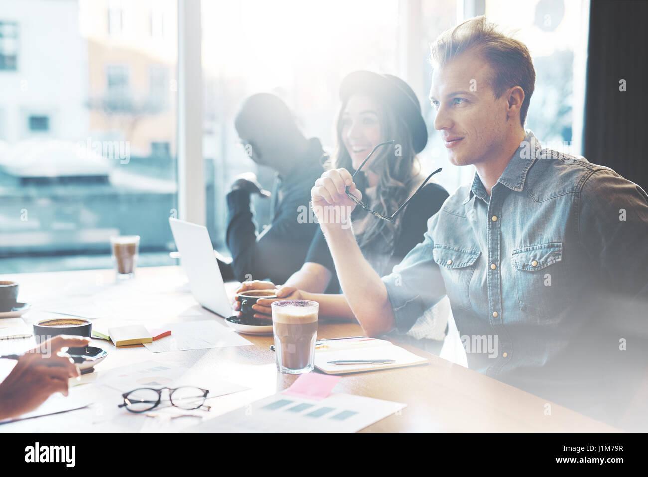 Bel giovane uomo caucasico nell incontro al grande tavolo da conferenza in ufficio con finestre luminose Immagini Stock