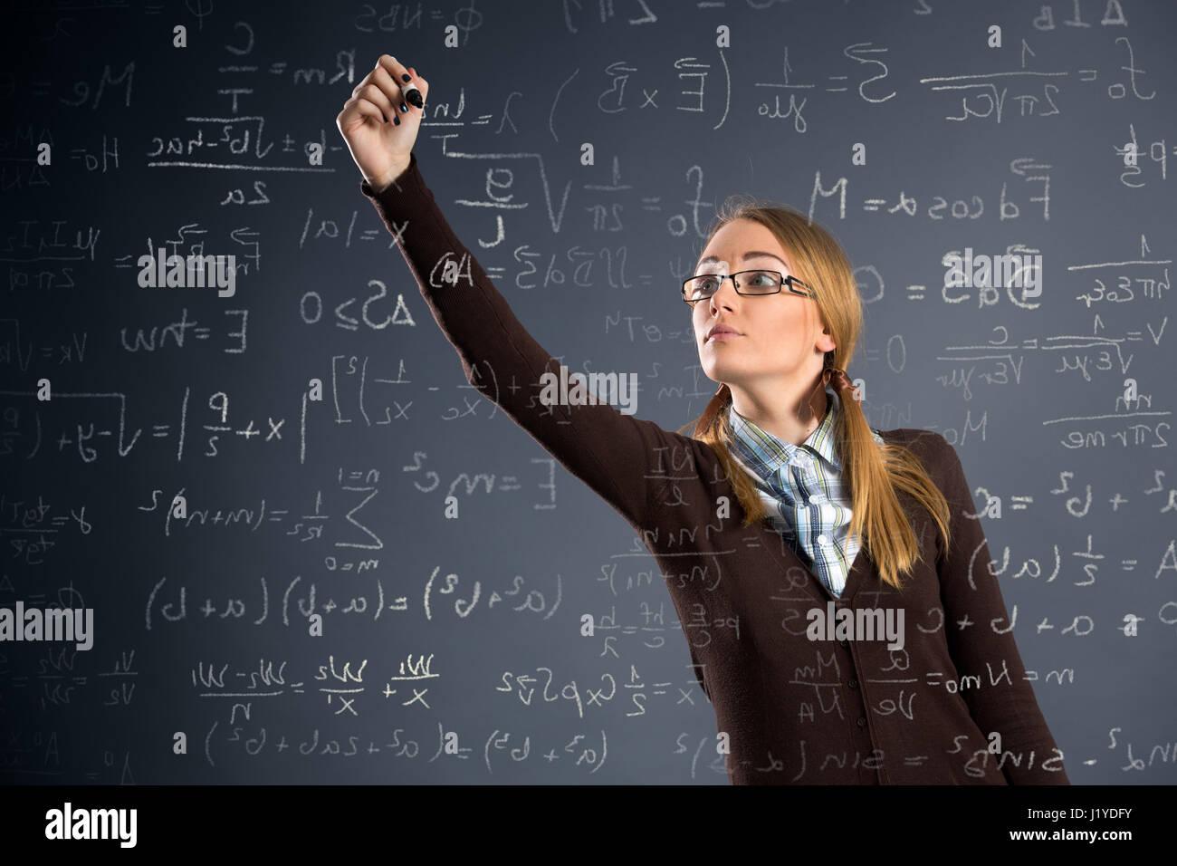 La scolaretta assegnazioni di lavoro di matematica sulla parete trasparente Immagini Stock
