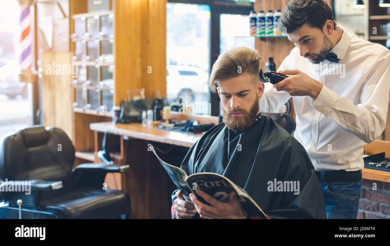 Giovane uomo in Barberia per la cura dei capelli il concetto di servizio Immagini Stock