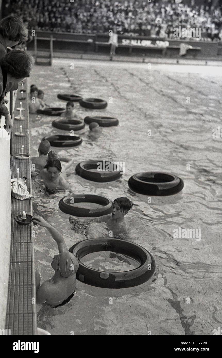 Degli anni Cinquanta, i ragazzi in piscina a lato con i loro anelli di gomma, ottenere pronto a prendere parte alla Immagini Stock