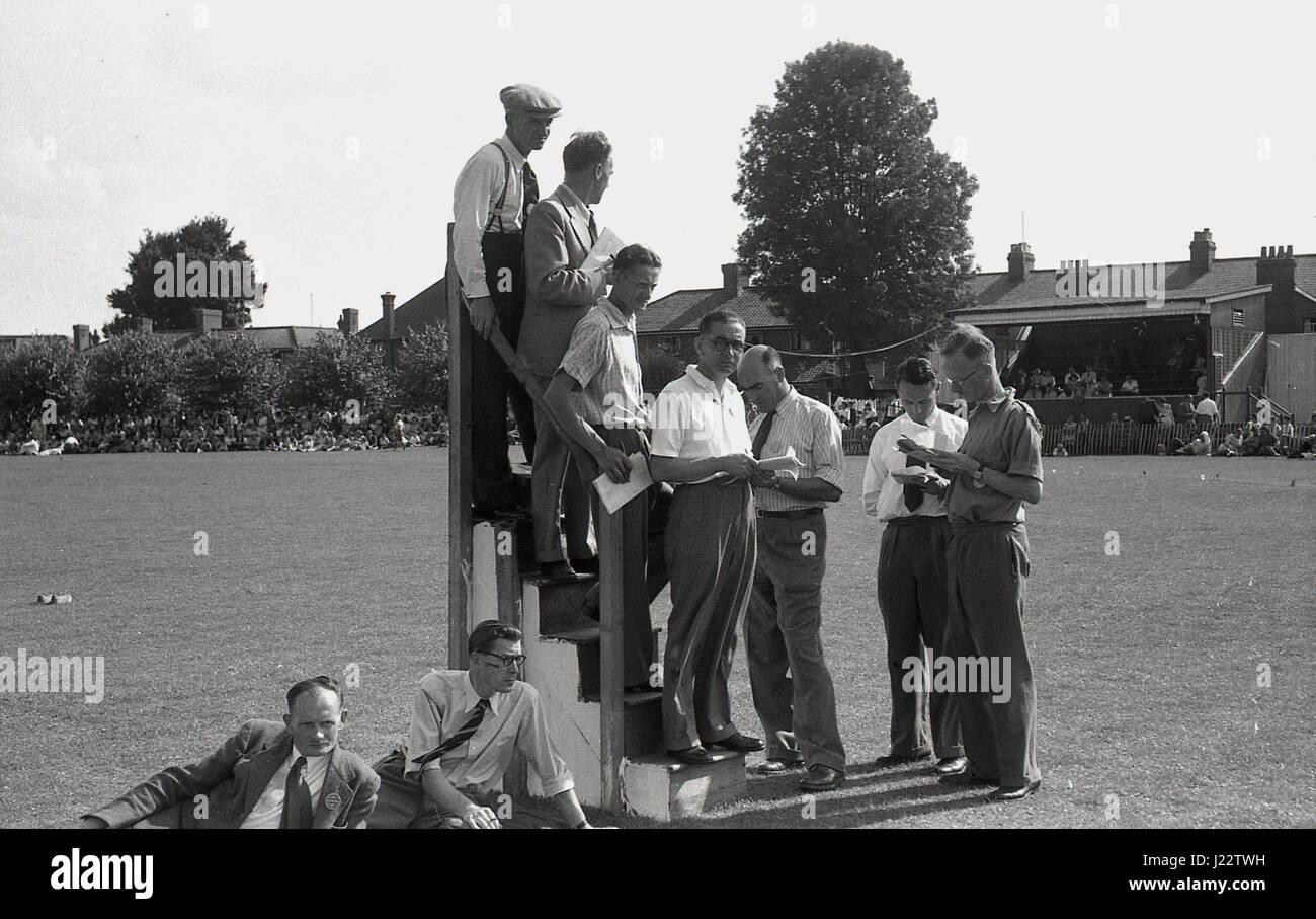 Degli anni Cinquanta, storico cronometristi su un cavalletto di cronometraggio a un dilettante outdoor meeting di Immagini Stock